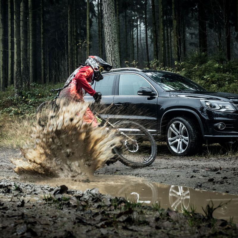 Christian Junker riding his mountain bike next to his black VW Tiguan 1 with bike rack