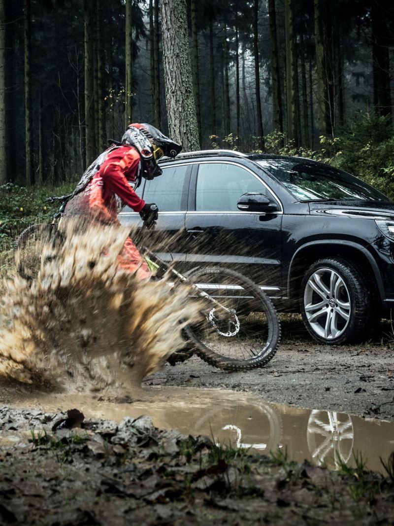 Christian Junker fährt auf seinem Mountainbike neben seinem schwarzen VW Tiguan 1 mit Fahrradträger