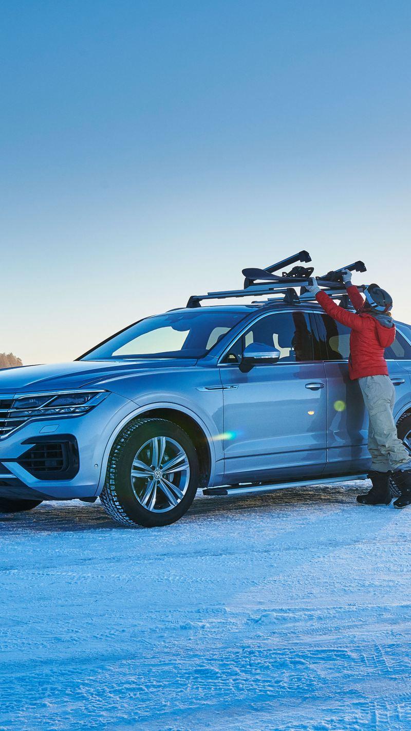 Una Volkswagen parcheggiata su un campo innevato con pneumatici invernali.