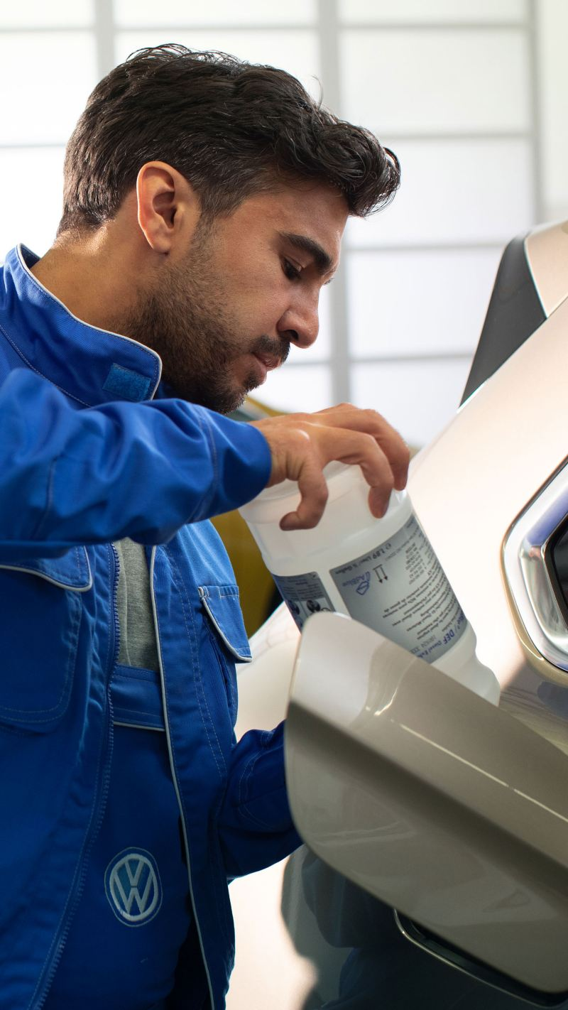 A VW service employee refills AdBlue® into a VW vehicle – Volkswagen operating fluids