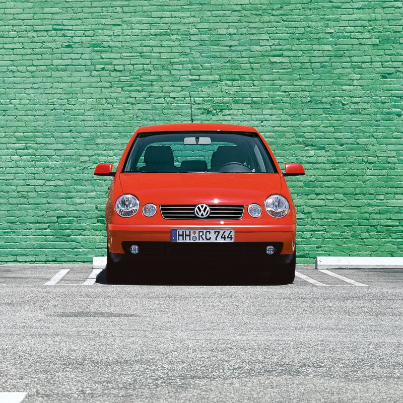 A parking red VW Polo 4 type 9N1 in front of a green wall