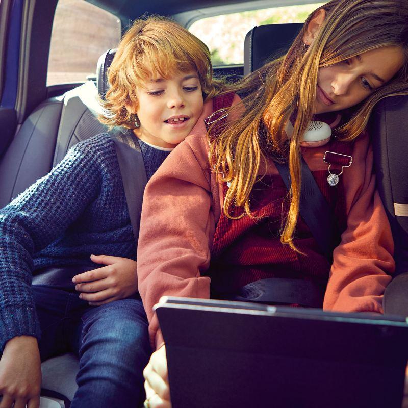 Bambini guardano un tablet seduti sul sedile posteriore di una Volkswagen
