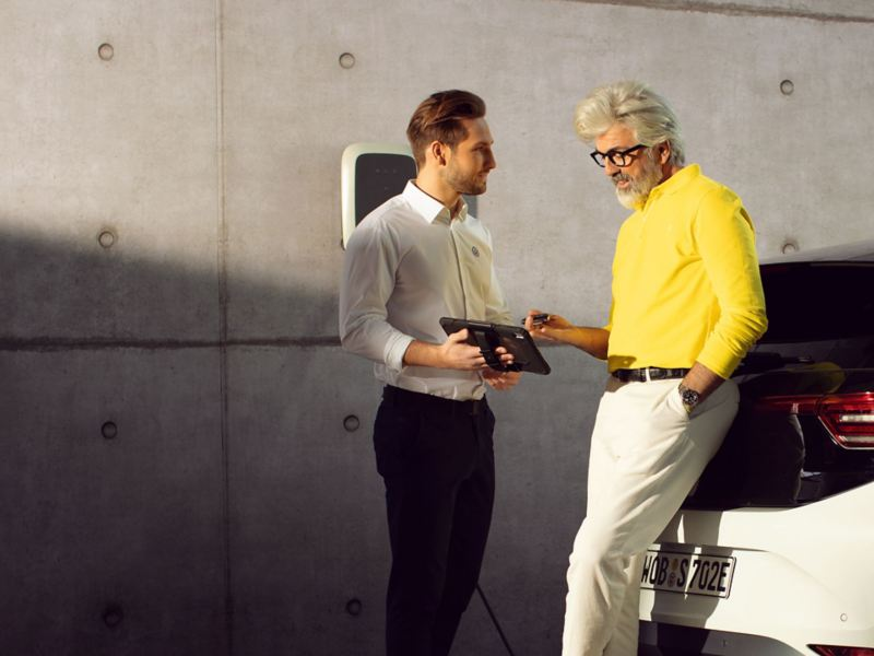 A VW employee speaks with an owner about their electric vehicle service