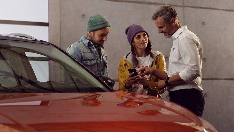 Ein VW Mitarbeiter klärt seine Kunden über Serviceleistungen auf, davor ein VW Auto – Zubehör- und Serviceangebote