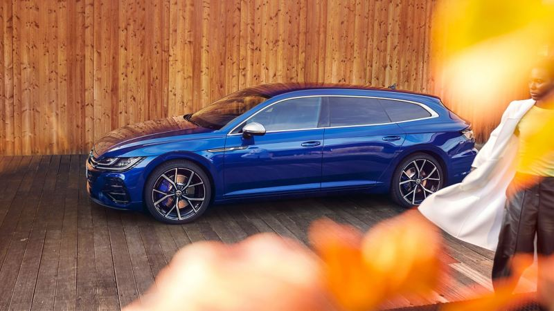 A VW Arteon R Shooting Brake in blue, parked in front of a wooden fence