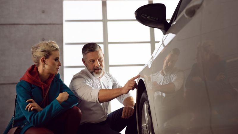 A VW service employee shows his customer new vehicle body parts added to her car
