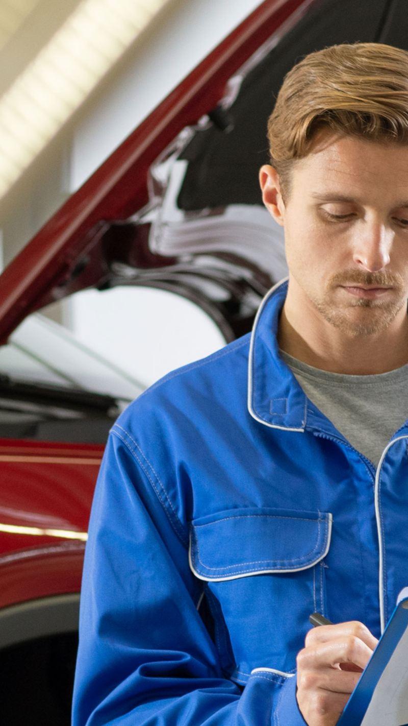 Un Réparateur Agréé Volkswagen vérifie une checkliste entretien devant une Volkswagen rouge dont le capot est ouvert
