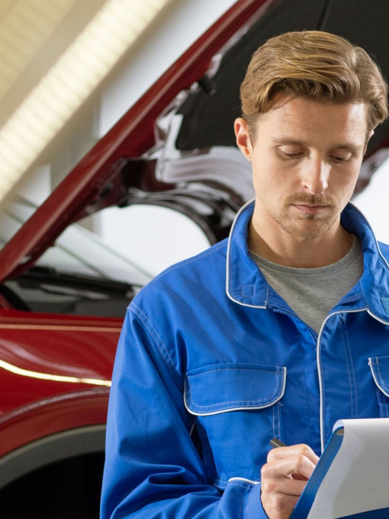 "Man in the VW uniform looking at the report, link out to VW ""service"" page"