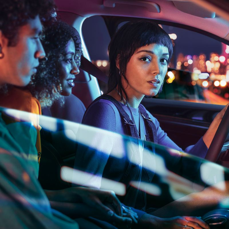 A group of friends sits in her VW car and parks in front of a nightly skyline – Volkswagen battery