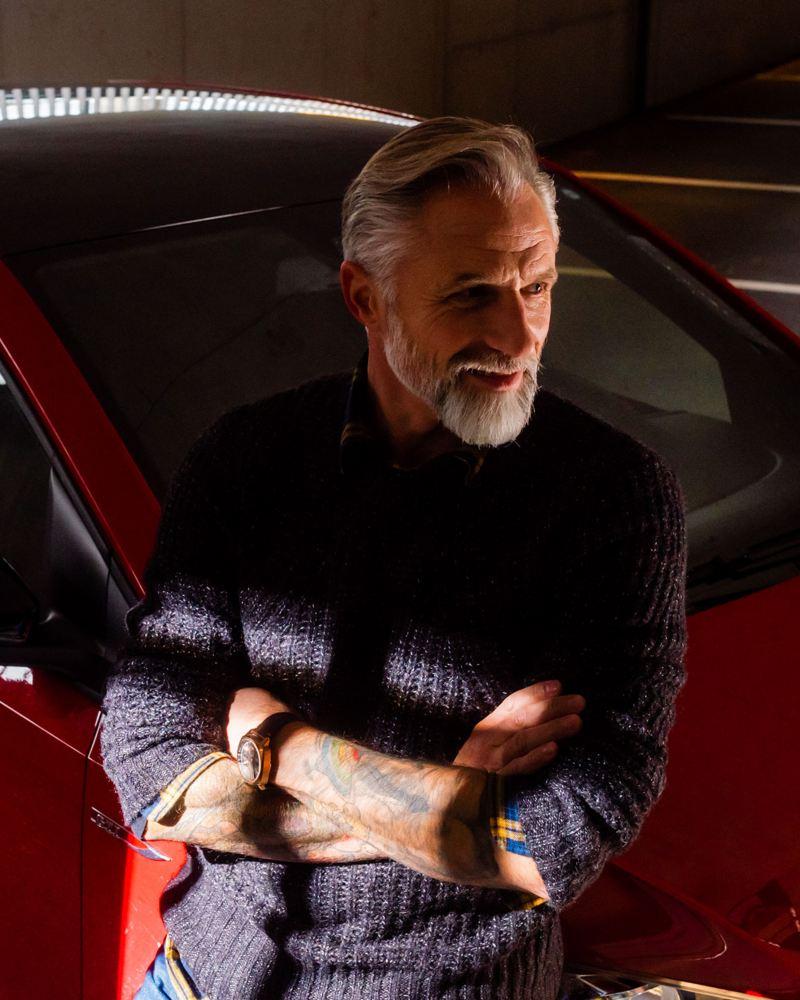 Uomo con le braccia incrociate appoggiato al cofano di un auto VW