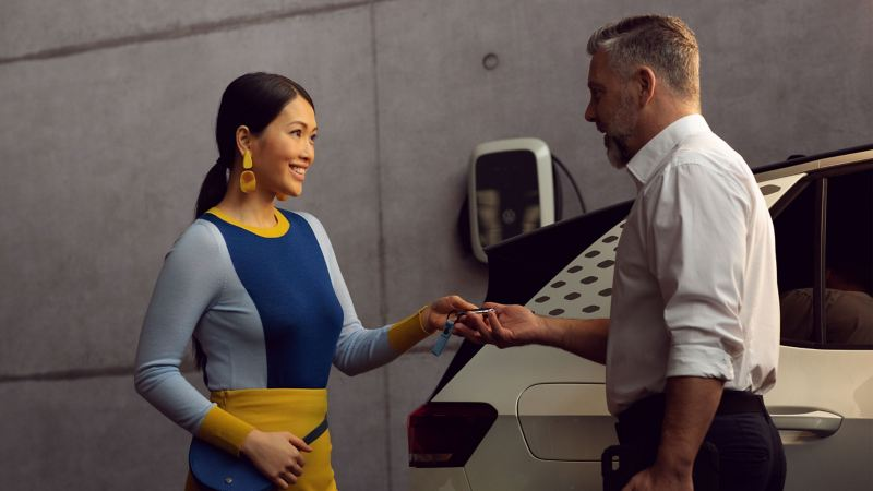 A VW service employee hands a customer the key to her VW ID.3