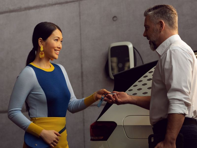 A VW employee handing over their ID. to a customer