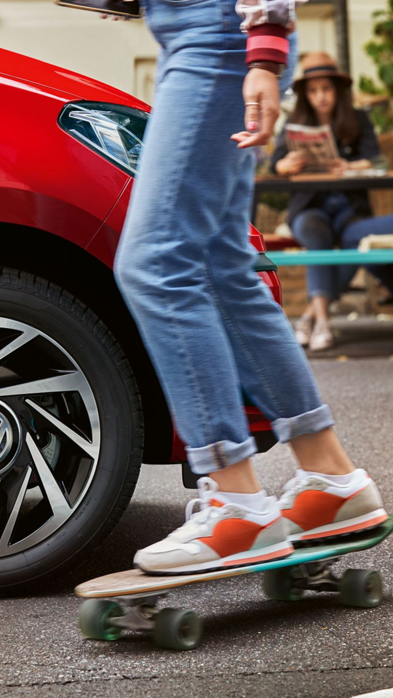 A woman on a skateboard drives past a red VW up! Join with summer tyres