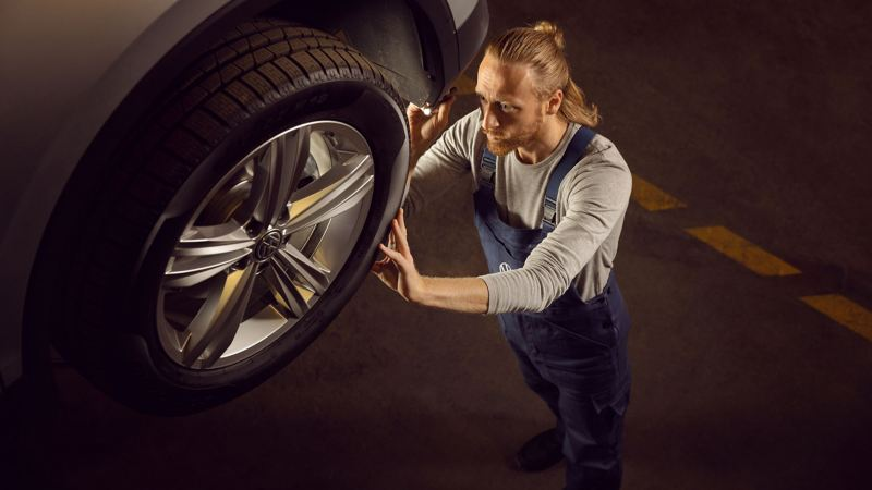 A VW service employee takes care of the wheels on a Volkswagen car – wheel knowledge