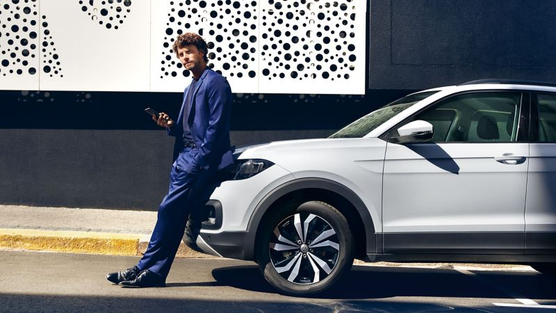 A man with a smartphone leans against his white VW car with polished rims – Volkswagen wheels and tyres