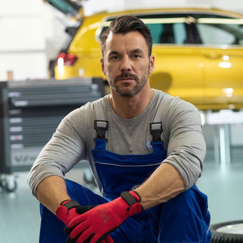Un employé de service VW est assis sur une pile de pneus dans un atelier.