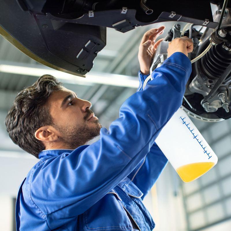 Meccanico esegue cambio liquido freni su una Volkswagen sul ponte