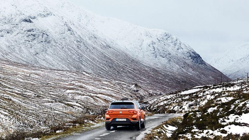 Volkswagen orange sur la route dans un paysage enneigé