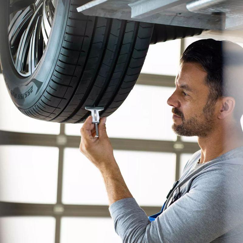 Technicienne Volkswagen vérifiant l'usure d'un pneumatiques