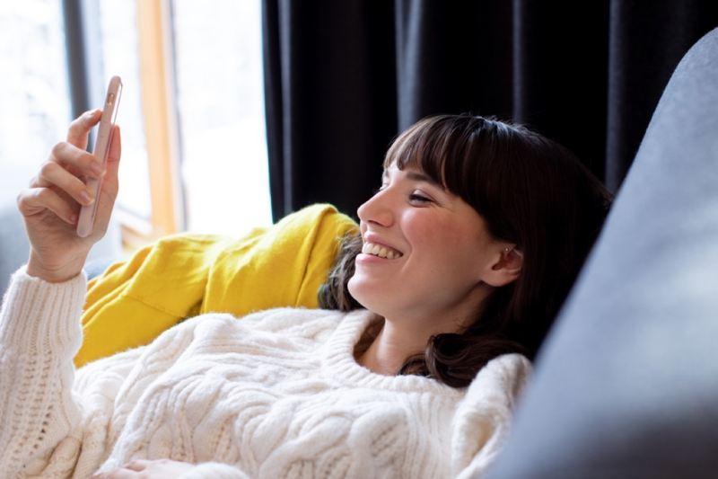 Chica sonriendo con un teléfono en la mano tumbada en un sofá