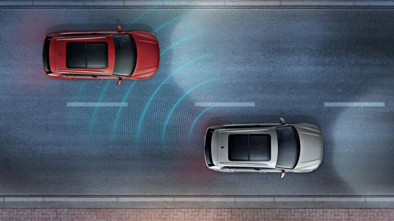 Due Volkswagen di notte su una strada viste dall'alto. Il funzionamento dei sensori del sistema di assistenza al cambio di corsia Side Assist è rappresentato da linee
