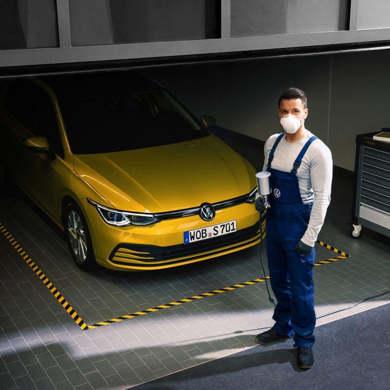 Skadespecialist står framför gul Volkswagen i ett garage
