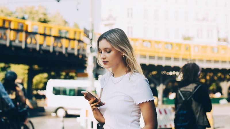 Ragazza utilizza lo smartphone in centro città