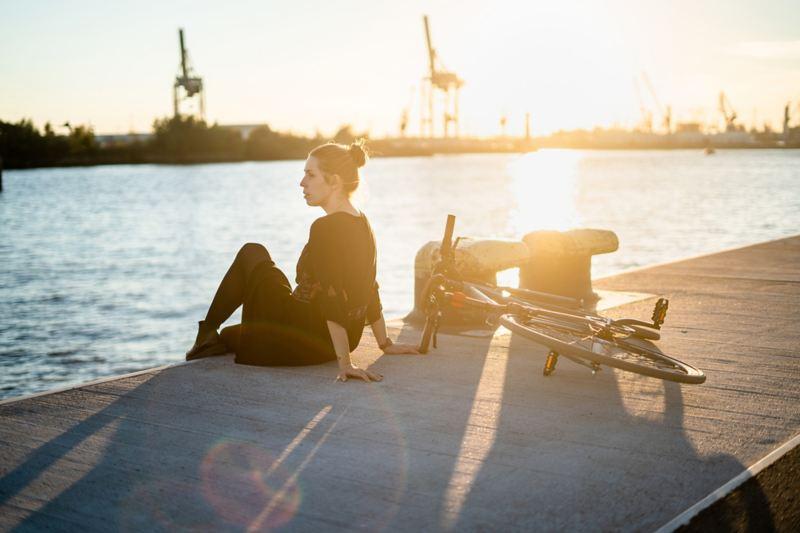 Una donna seduta al porto di Amburgo, accanto a lei una bicicletta