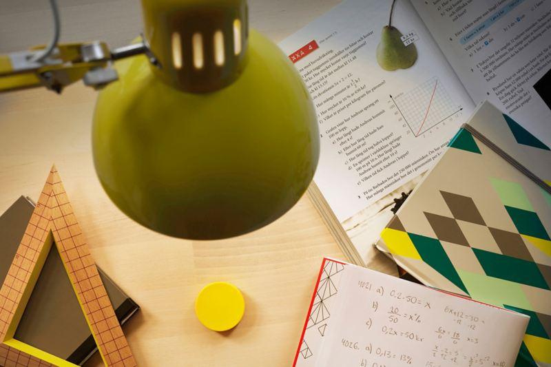 Lampe leuchtet auf Tisch auf dem Bücher liegen.