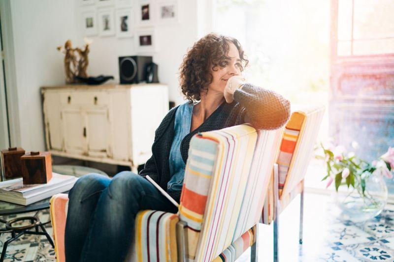 Donna seduta in un salotto assolato