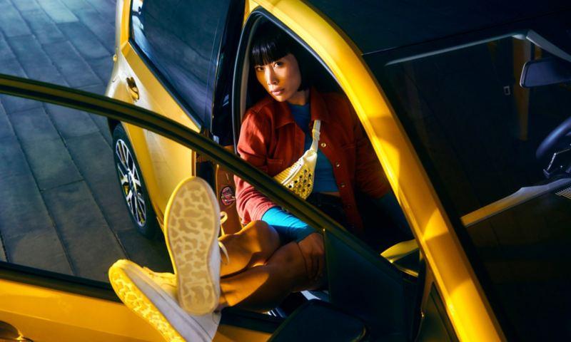 Una ragazza, con i piedi appoggiati al finestrino della portiera aperta, siede sul sedile passeggero anteriore di Volkswagen Nuova e-up!, vista frontalmente dall'alto.