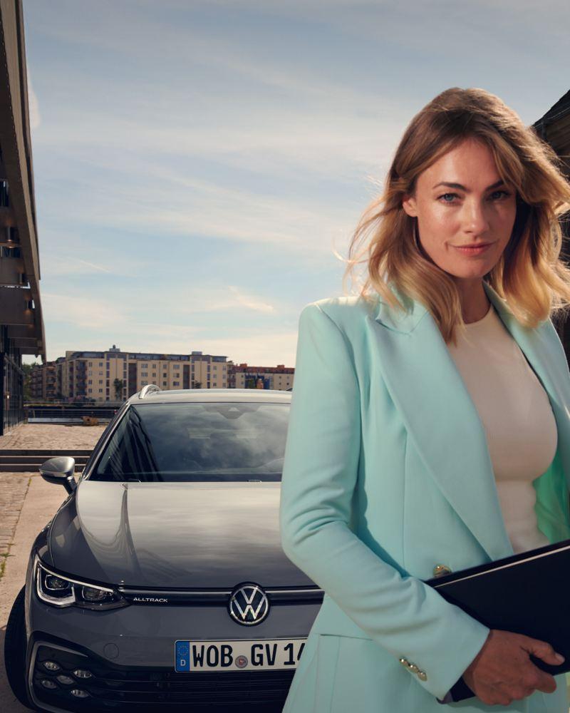 Donna elegante davanti alla Volkswagen Golf 8 Alltrack per uso aziendale.