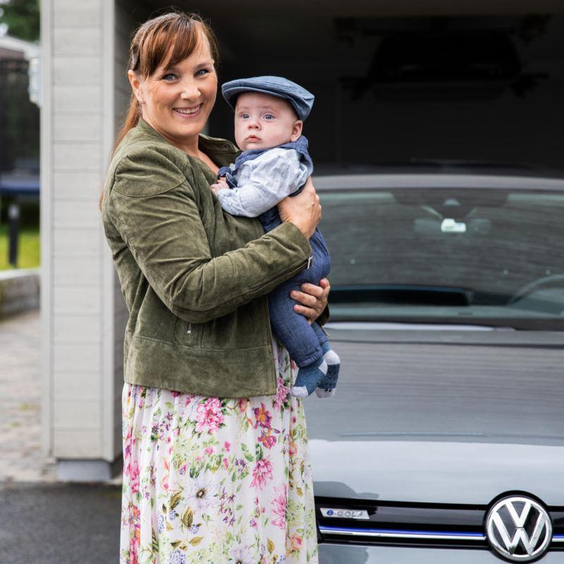 En kvinne bærer et barn foran e-Golf elbil med lakkbeskyttelse