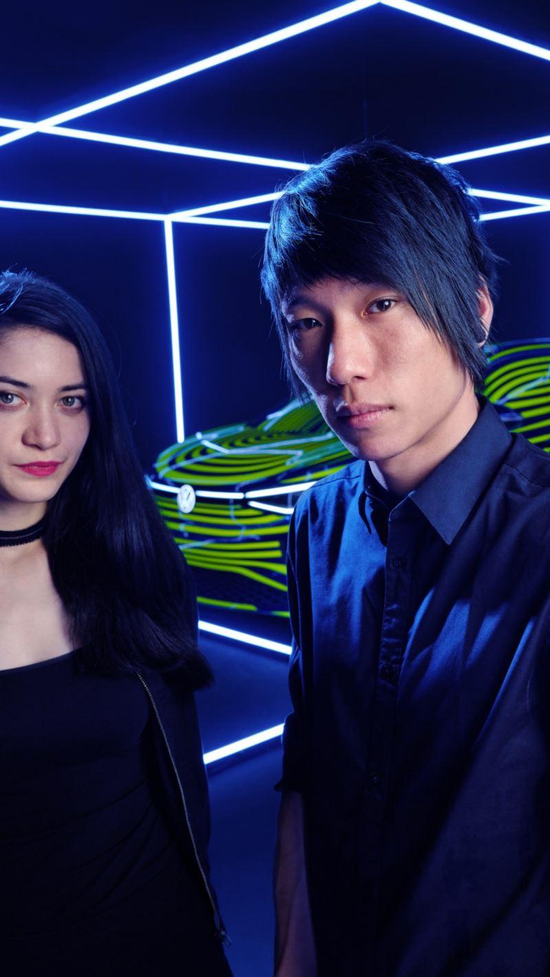 Nahaufnahme der Designer Noemi Schipfer und Takami Nakamoto vor dem in Szene gesetzten ID.4