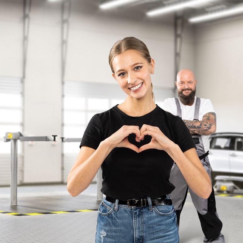 Junge Frau herzt glücklich einen Werkstattmitarbeiter