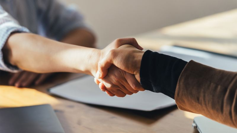 Two people shaking hands on an agreement