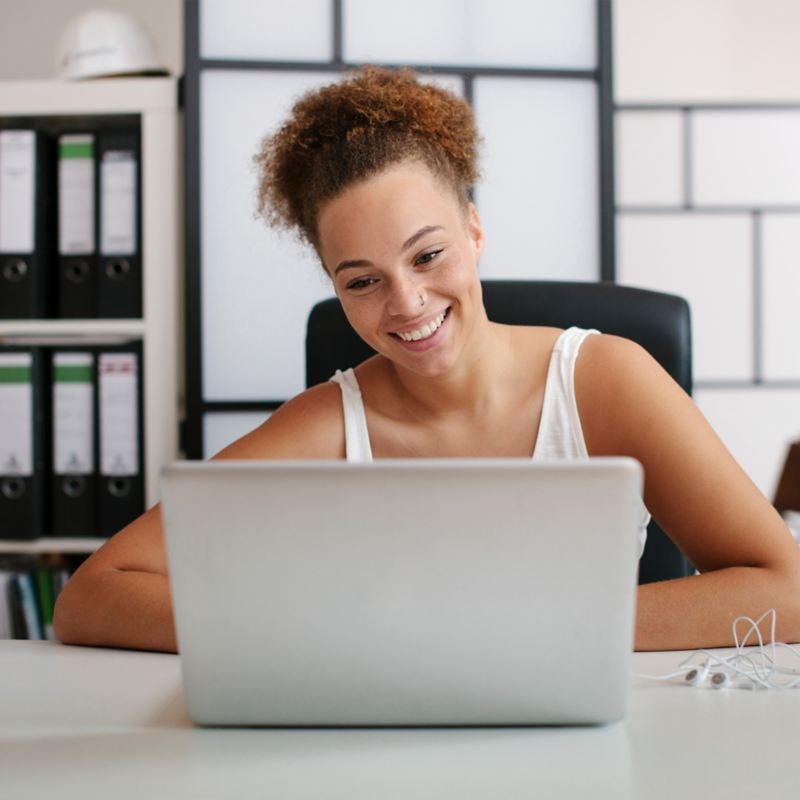 A young woman sitting at a desk in front of her laptop