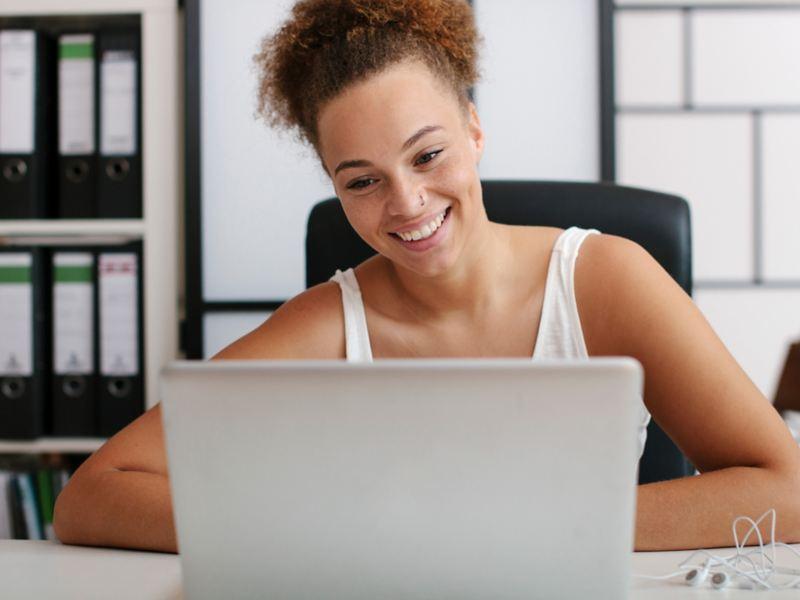 Lächelnde Frau sitzt an einem Schreibtisch und schaut auf ihren Laptop