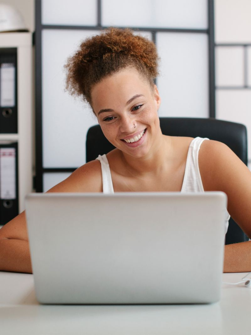 Smiling woman sitting at a desk and looking at her laptop