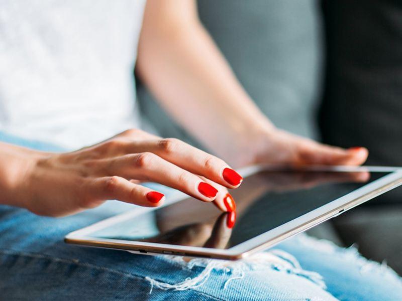 Eine junge Dame mit roten Fingernägeln benutzt ihr Tablet