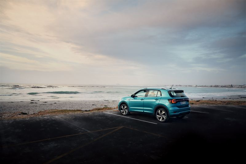 Woman leaning against a VW T-Cross at a beach