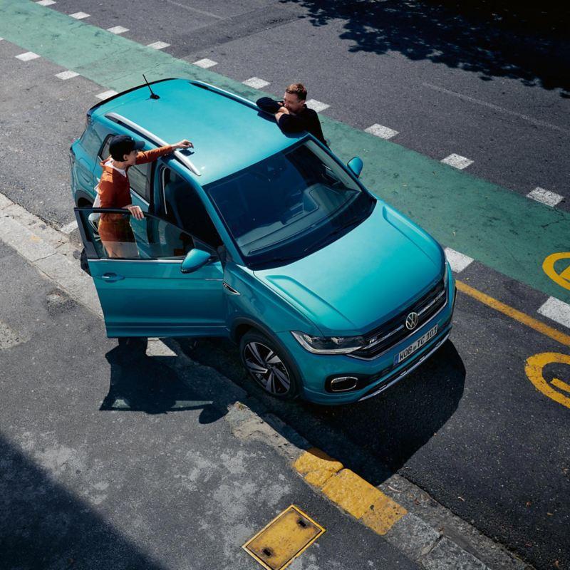 Mann lehnt vor VW T-Cross Front, oranges Fahrzeug in Stadtkulisse