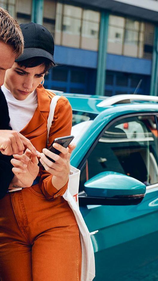 En kvinna och en man står lutade mot en VW T-Cross och tittar ner i en smartphone