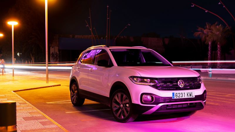 The white T-Cross in the neon light of the city