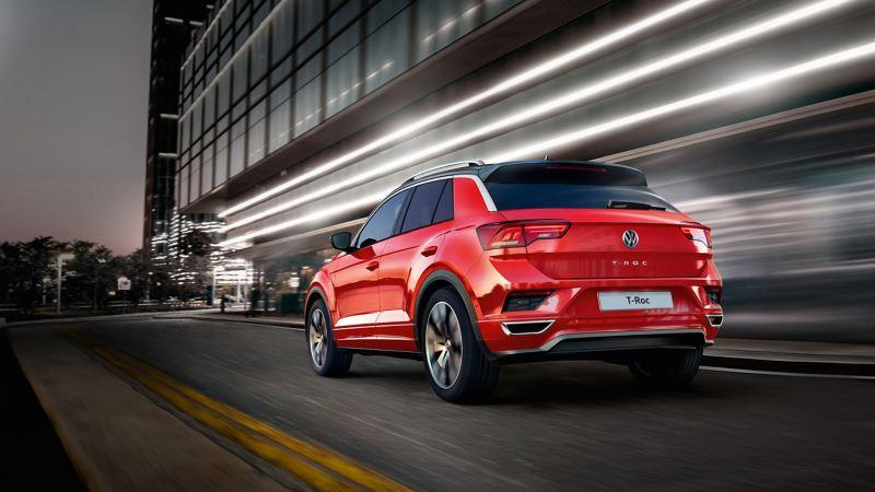 Volkswagen T-Roc Style e Volkswagen T-Roc Advanced in città di notte ad un incrocio a T