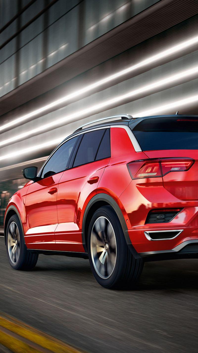 Vista posteriore di Volkswagen T-Roc rossa corre in città di notte