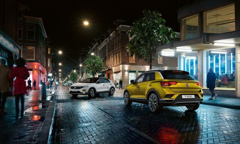 Ein gelber T-Roc fährt in der Nacht durch die Stadt