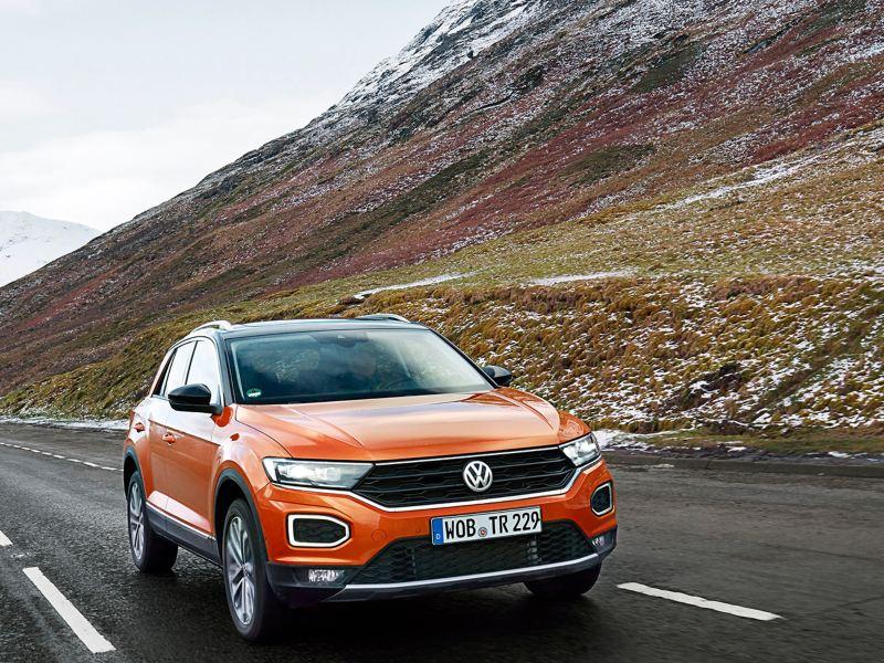 Fahrender VW T-Roc in den Highlands von Schottland auf einer Straße am Hang