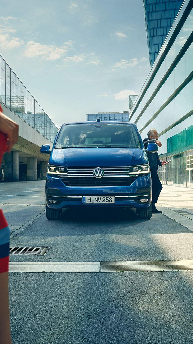 vw Volkswagen blå Caravelle varebil flyplass dame krysser gaten mann i blå dress