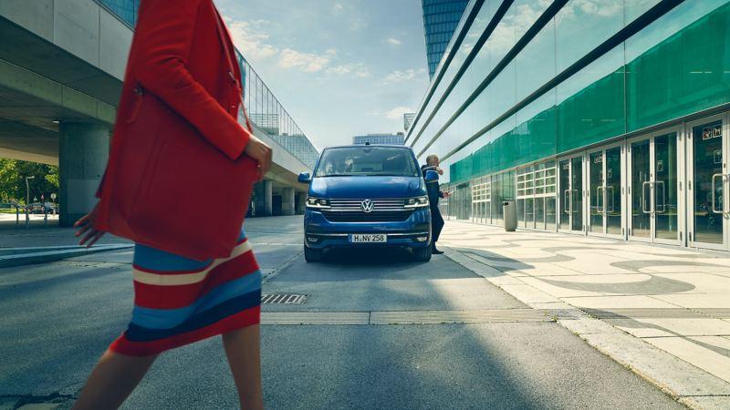 Bildet viser en blå Volkswagen Caravelle varebil som står parkert foran en flyplass